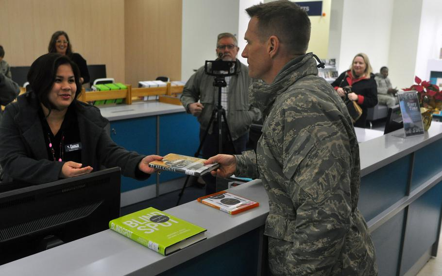 Brig. Gen. Lance Landrum, commander of the 31st Fighter Wing, officially checks out the first book from the new base library at Aviano Air Base, Italy, on Friday, Jan. 6, 2017, with the help of library technician Madona Solana.