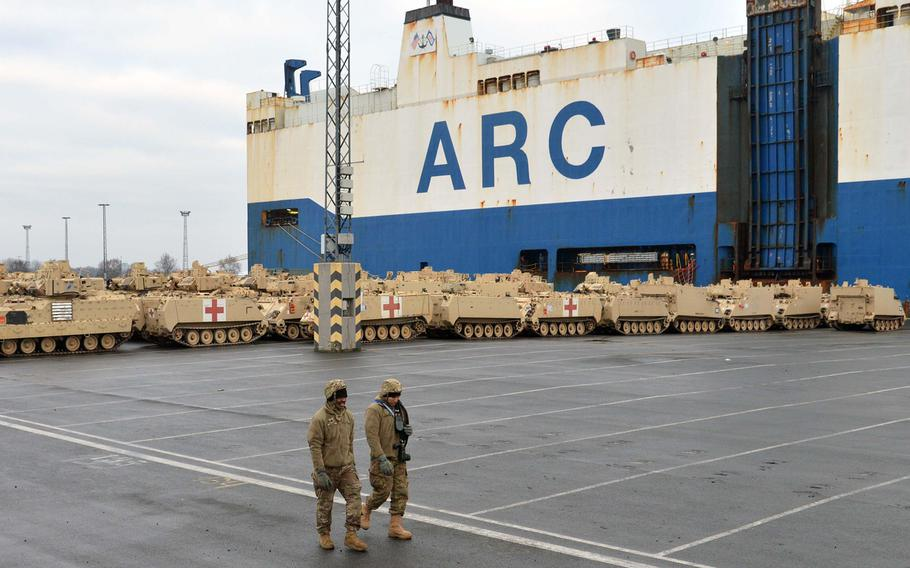 Two soldiers walk past armored vehicles at the port of Bremerhaven, Germany, on Sunday, Jan. 8, 2017. The 3rd Armored Brigade Combat Team, 4th Infantry Division, out of Fort Carson, Col., is headed to Poland for a nine-month rotation as part of Operation Atlantic Resolve.