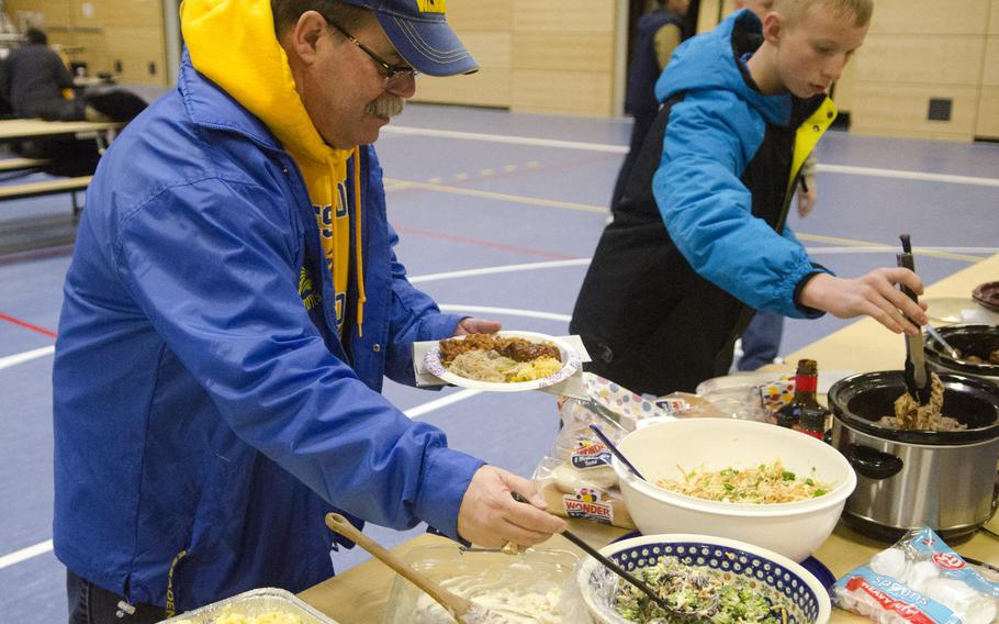 Greg Hatch, principal of Wiesbaden High School, takes some of a potluck dinner at the school's robotics club's season kickoff party, Saturday, Jan. 7, 2017, in Wiesbaden. The potluck preceded the announcement of the theme and specifications for the FIRST Robotics Competition.