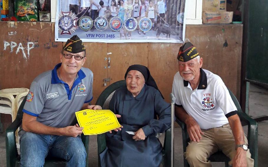 Norme Smith, left, Veterans of Foreign Wars Post 2485 commander, and John Gilbert, Department of the Pacific commander, present sister Alessandria Casas with $5,000 to help build an orphanage near Clark Air Base, Philippines.