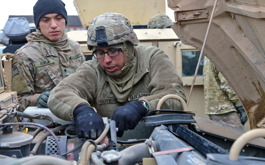 Spc. Jose Ayala, left, watches Sgt. Kevin Gutierrez make adjustments on a Humvee, near Bergen, Germany, after driving from Bremerhaven on their way to Poland, on Monday, Jan. 9, 2017. Both soldiers are with 1st Battalion, 8th Infantry Regiment, 3rd Armor Brigade Combat Team, 4th Infantry Division.