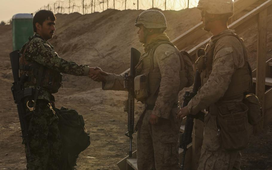 U.S. Marines with Alpha Company, 1st Battalion, 2d Marine Regiment, greet a member of the Afghanistan National Army as he takes post at Camp Leatherneck, Helmand province, Afghanistan, Oct. 27, 2014. The battalion was the final Marine Corps infantry battalion to serve in Helmand province as the Marine Corps turned over operations to the ANA.