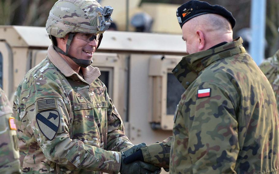 Polish Maj. Gen. Jaroslaw Mika, right, commander, 11th Armoured Cavalry Division, greets Col. Christopher Norrie,3rd Armored Brigade Combat Team, 4th Infantry Division commander, after a convoy of the unit's vehicles crossed the German-Polish border at the Olszyna crossing, Thursday, Jan. 12, 2017.