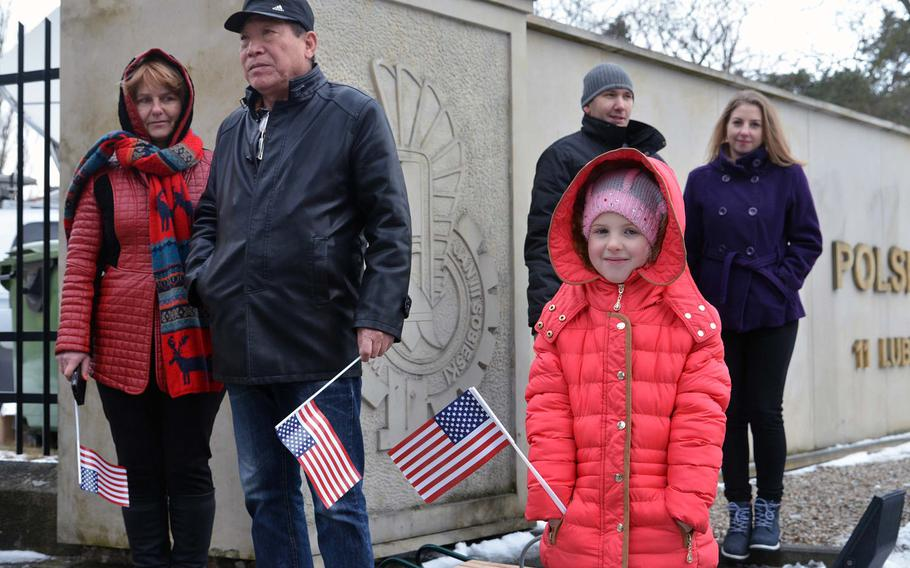 Spectators hold American flags during a welcoming ceremony for soldiers of the 3rd Armored Brigade Combat Team, 4th Infantry Division, in Zagan, Poland, Thursday, Jan. 12, 2017.