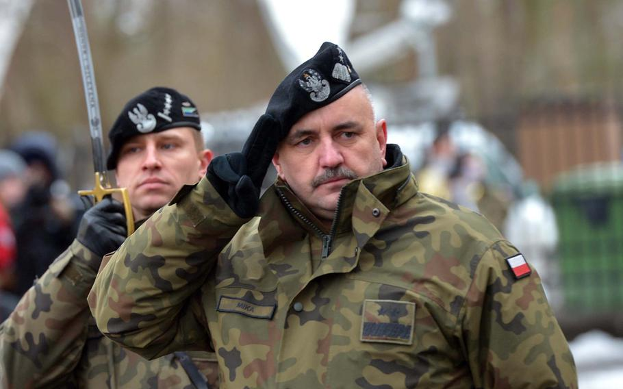 Polish Maj. Gen. Jaroslaw Mika, commander, 11th Armoured Cavalry Division, salutes American troops of the 3rd Armored Brigade Combat Team, 4th Infantry Division, during a welcoming ceremony for the Americans in Zagan, Poland, Thursday, Jan. 12, 2017.