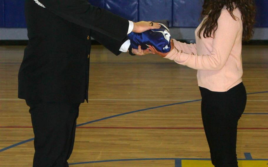 Amaya Wasai, an eighth-grader at Sigonella Middle/High School in Sicily, Italy, receives a folded U.S. flag during a ceremony Tuesday, Jan. 10, 2017, at the school. Amaya is one of 20 students from Sigonella traveling to Washington to participate in the presidential inaugural parade on Jan. 20.