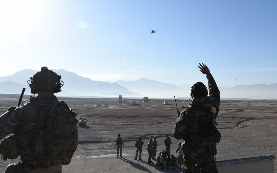 A student in a training program for Afghan Tactical Air Coordinators waves at an MD-530 attack helicopter during a live-fire exercise at a range south of Kabul, on Dec. 27, 2016.