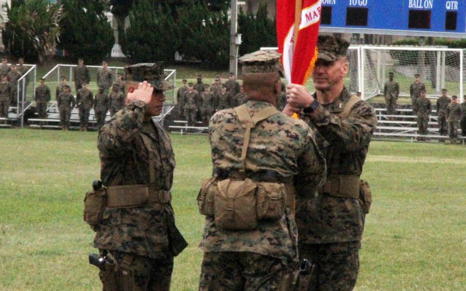 Maj. Gen. Richard Simcock II, right, the outgoing 3rd Marine Division commander, passes the division banner to  Maj. Gen. Craig Timberlake during a change-of-command ceremony at Camp Courtney, Okinawa, Friday, Jan. 20, 2017. Sgt. Maj. Vincent Santiago, left, the division's top enlisted leader, salutes.