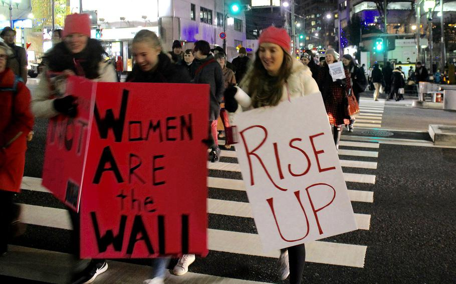 Marchers hold signs as they cross the street in central Tokyo on Jan. 20, 2017.