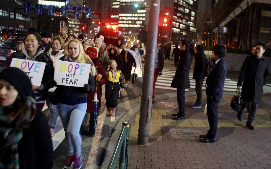 Tokyo office workers wait to cross as the Women's March in Tokyo procession continues on Jan. 20, 2017.