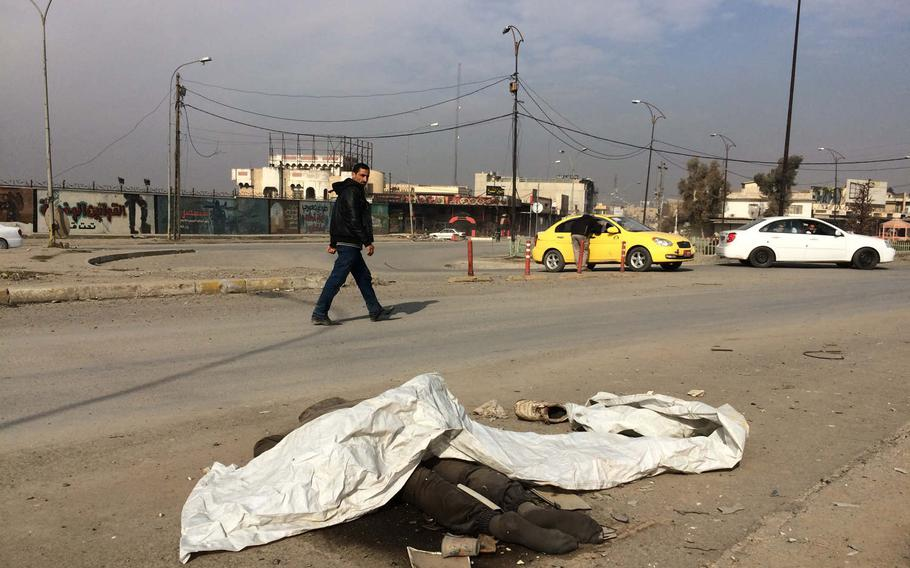 Traffic passes the body of a person locals said was an Islamic State fighter, near Mosul University on Saturday, Jan. 21, 2017.