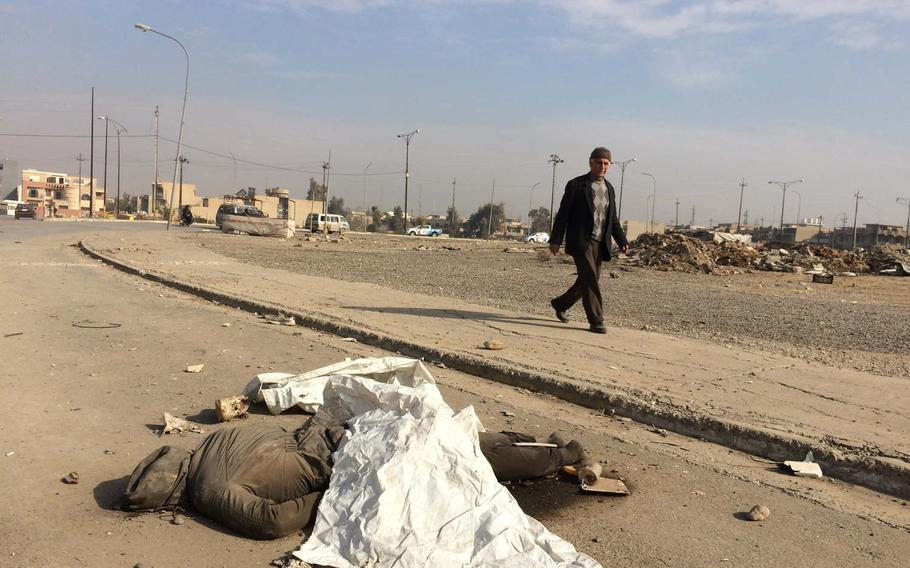 A pedestrian passes the body of a person locals said was an Islamic State fighter, near Mosul University on Saturday, Jan. 21, 2017.