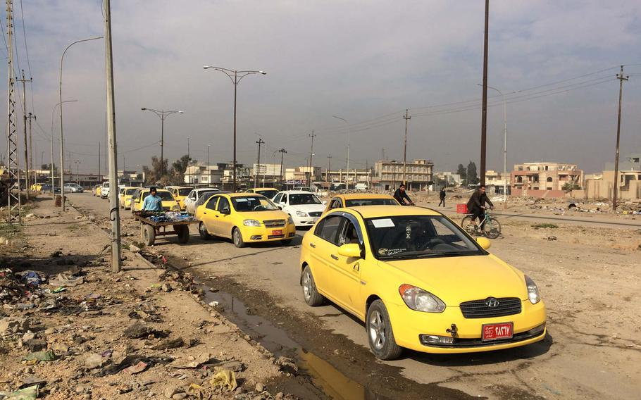 Cars and bicycles pass along a road near Mosul University on Saturday, Jan. 21, 2017.