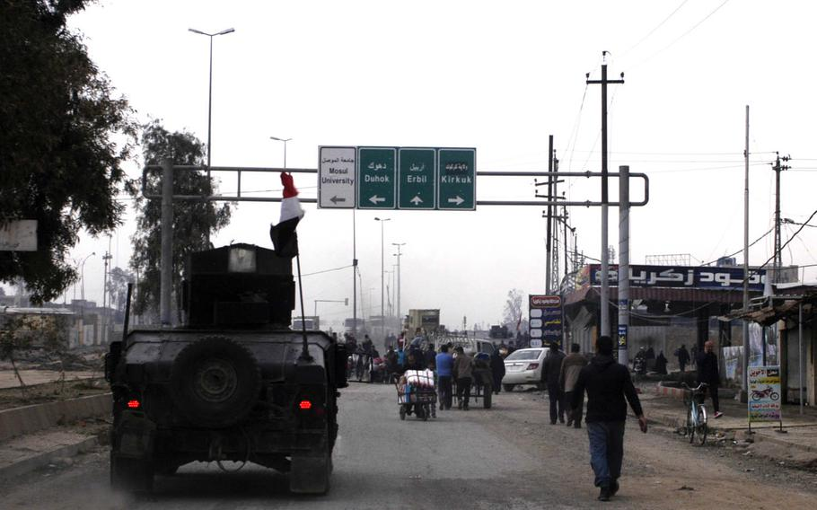 An Iraqi special forces Humvee passes pedestrians in Mosul on Saturday, Jan. 21, 2017.