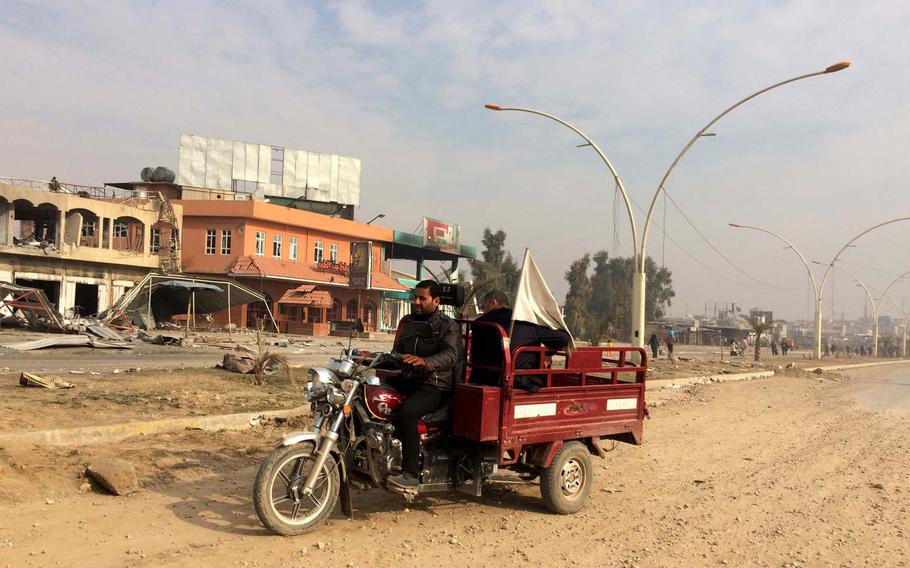 A motorcycle with a white flag drives through a liberated neighborhood in Mosul, Iraq, on Saturday, Jan. 21, 2017.