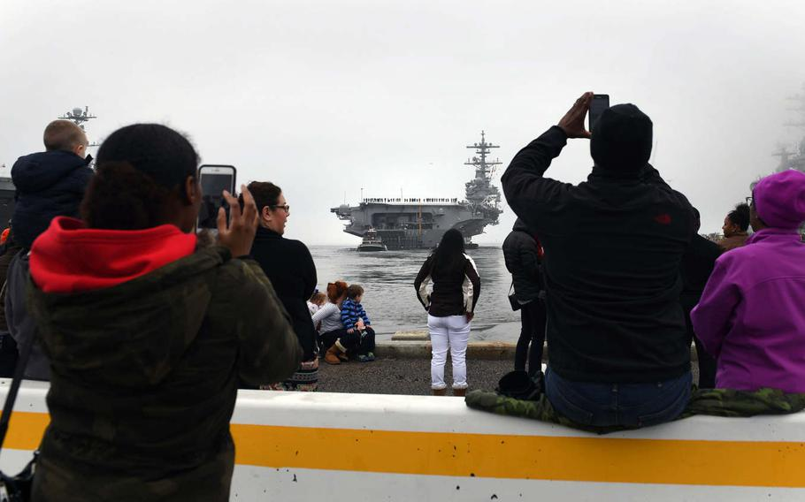 Family members and friends take pictures from the pier as aircraft carrier USS George H.W. Bush departs Naval Station Norfolk, Va., for a deployment to the 5th and 6th Fleet areas of operation, Saturday Jan. 21, 2017.