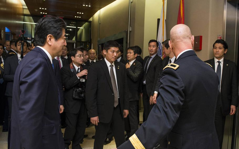 Japanese Prime Minister Shinzo Abe, left, tours the Defense POW/MIA Accounting Agency in Hawaii.