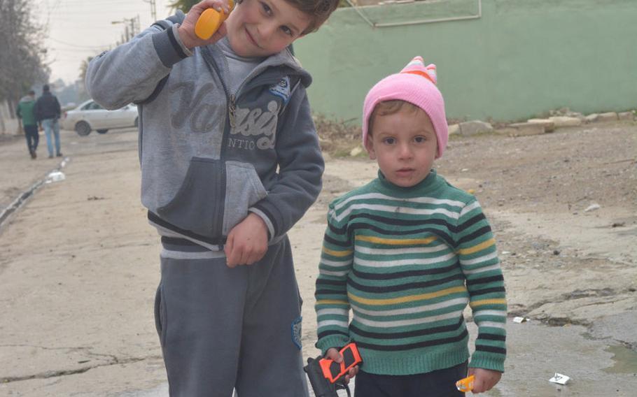 Kids with toy guns play in Mosul's Hay al-Arabi neighborhood Wednesday, Jan. 25, 2017.