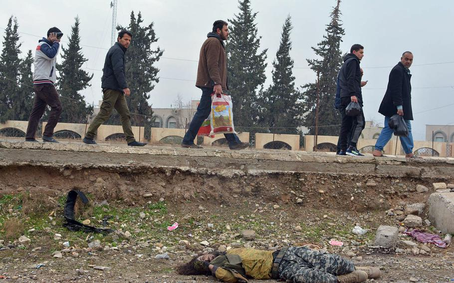 Residents pass a dead Islamic State fighter in Mosul's al-Arabi neighborhood on Wednesday, Jan. 25, 2017. What appears to be a suicide bomb vest lies near the body.