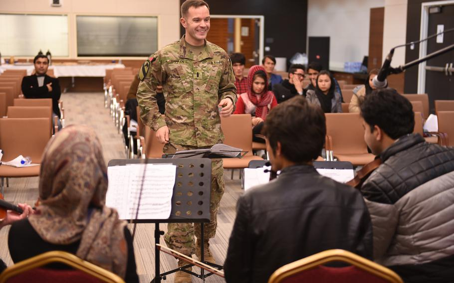U.S. Army 1st. Lt. Philip Tappan, of the U.S. Forces Afghanistan Band, leads a rehearsal for a joint concert with music students and instructors from Kabul University at the U.S. Embassy in Kabul, Wednesday, Jan. 25, 2017.