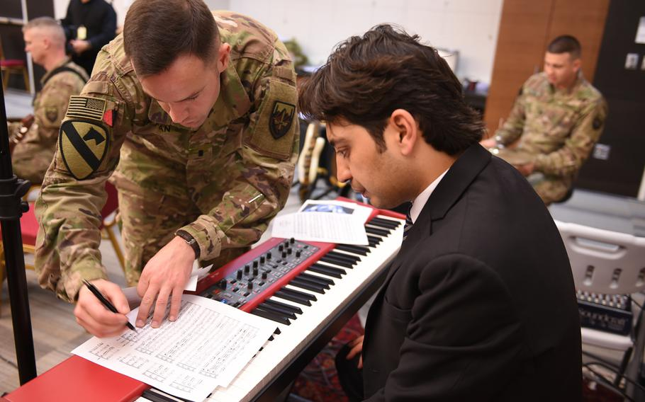1st Lt. Philip Tappan of the U.S. Forces Afghanistan Band gives direction to Ghafar Maliknezhad, an assistant music professor at Kabul University, during a rehearsal for a joint concert with the band and university students and instructors, Wednesday, Jan. 25, 2017.