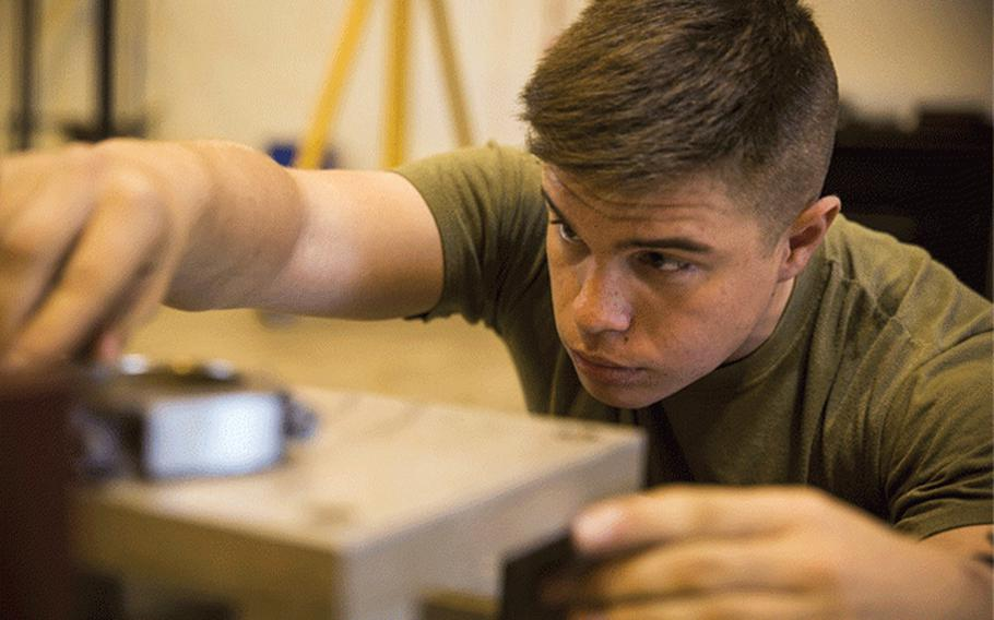 Cpl. Matthew A. Long checks connecting rods for the crank shaft of a High Mobility Multipurpose Wheeled Vehicle, Nov. 8, 2016, at Camp Kinser, Okinawa, Japan. Marines took apart, cleaned, and assembled an engine of a HMMWV. Long, a Moultrie, Georgia native, is an automotive maintenance technician with 3rd Marine Logistics Group, III Marine Expeditionary Force. (U.S. Marine Corps photo by Cpl. Nathaniel Cray / Released)