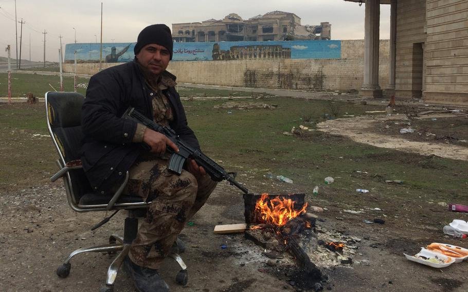 An Iraqi soldier keeps warm in front of a palace in Mosul, Iraq, on Wednesday, Jan. 25, 2017. The mural behind him depicts the Islamic State group's dream of the conquest of Rome.
