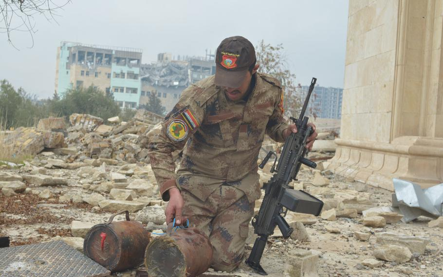 A soldier pulls improvised explosive devices out of a hole beside a palace overlooking the Tigris River in Mosul, Iraq, on Wednesday, Jan. 25, 2017.