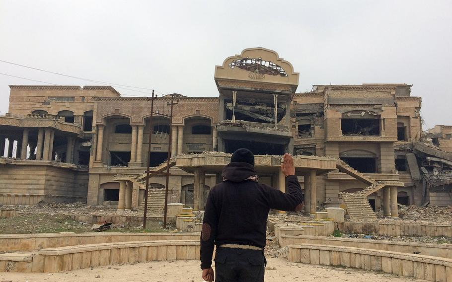 Iraqi special forces Capt. Aysar Ahmed Hassan, 36, poses in front of the wreck of a palace that was once U.S. Gen. David Petraeus' headquarters in Mosul, Iraq, on Friday, Jan. 27, 2017. On Independence Day, 2003, then Maj. Gen. David H. Petraeus, commander, 101st Airborne Division (Air Assault), administered the oath of reenlistment to more than 160 Screaming Eagle soldiers in front of the palace.