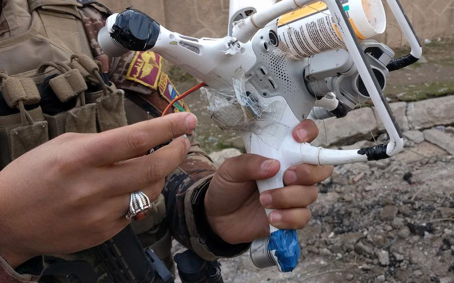 An Iraqi Counter Terrorism Service soldier in Mosul, Iraq, examines a quadcopter, modified by the Islamic State group to carry a 40 mm rifle grenade. Insurgent groups in Iraq started using handheld drones for surveillance two years ago. Now many of them have figured out how to arm them to attack adversaries.