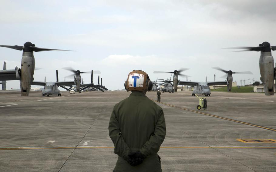 A Marine waits to guide MV-22 Ospreys with Marine Medium Tiltrotor Squadron 265, 31st Marine Expeditionary Unit, during their takeoff from Marine Corps Air Station Futenma, Okinawa.