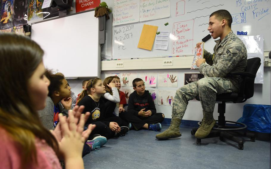 """Senior Airman Royer Figuereo reads Dr. Seuss' """"Did I Ever Tell You How Lucky You Are?"""" to fifth-graders at Ramstein Intermediate School in Germany on Thursday, March 2, 2017."""