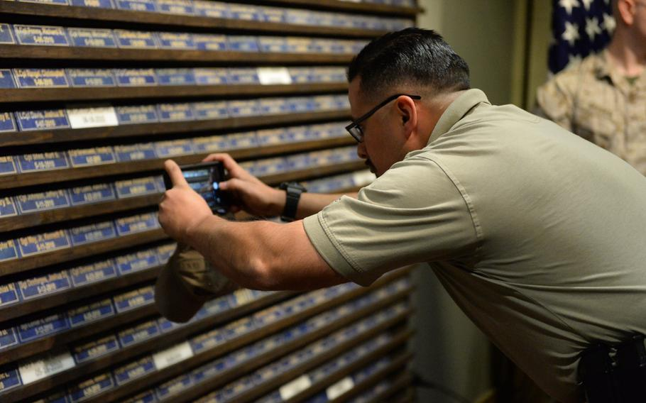 A man takes a photo of a memorial wall that includes the name of 482 of Marines and Navy corpsmen killed in Afghanistan since 2001, Thursday, March 2, 2017.
