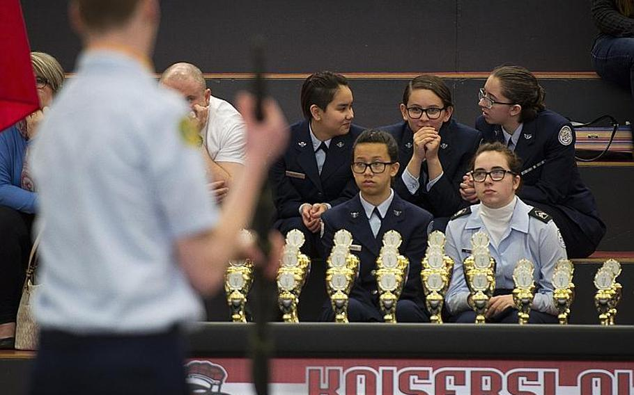 Cadets watch SHAPE's drill team perform in the armed team rifle exhibition during the DODEA-Europe JROTC drill team championships in Kaiserslautern, Germany, on Saturday, March 4, 2017. SHAPE won the event.