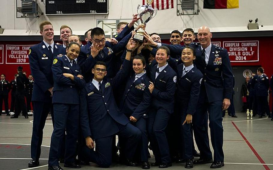 SHAPE's drill team hoists the overall team champion trophy in a group photo with Maj. Gen. Timothy Zadalis, U.S. Air Forces in Europe and Africa vice commander, right, during the DODEA-Europe JROTC drill team championships in Kaiserslautern, Germany, on Saturday, March 4, 2017. SHAPE also won seven other team and individual awards during the competition.