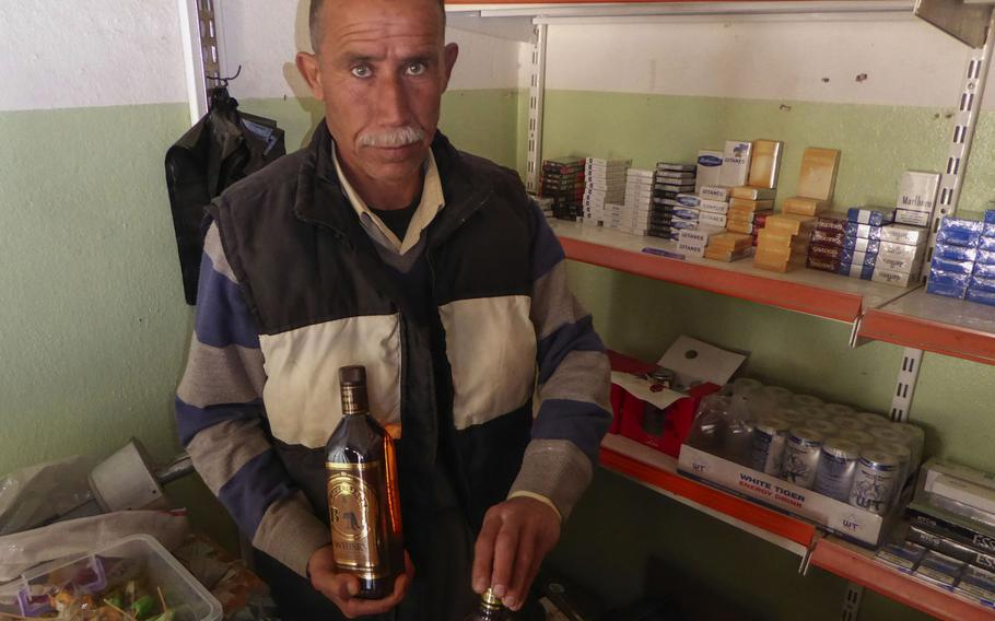 Yazidi Khiri Elias sells alcohol from a small shop in Bashiqa, Iraq, Monday, March 6, 2017. The village near Mosul was liberated in early November. Some families and businesses have begun returning, despite a great deal of destruction caused by fighting to oust Islamic State fighters who had held it since 2014.