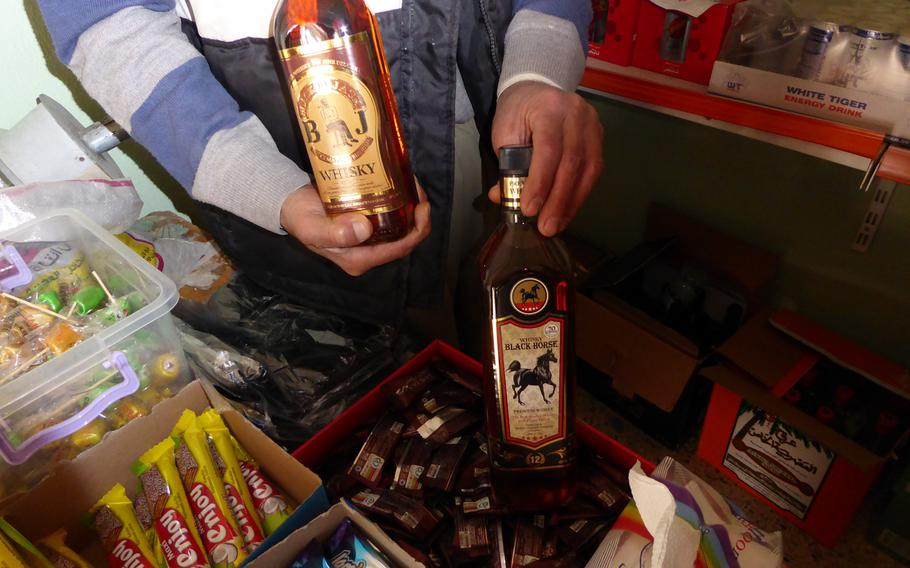 """Khiri Elias shows off Black Jack and Black Horse whiskey bottles that he sells from a small shop in Bashiqa, Iraq, Monday, March 6, 2017. The village, known as """"little Iraq"""" because its diverse population is a microcosm of the country, was liberated from roughly 2 1/2 years of Islamic State occupation in November and is slowly coming back to life."""