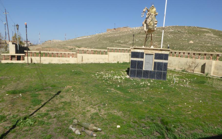 Mortars lie in the grass in front of a destroyed statue of a Yezidi hero in Bahzani, Iraq, Monday, March 6, 2017.