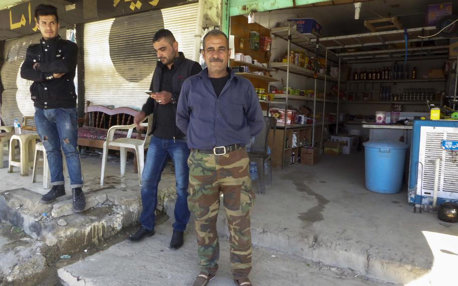Bassam Makhmoud stands in front of a shop in Bahzani, Iraq, Monday, March 6, 2017. Makhmoud sells snacks, sodas and some tools, but the most popular item in this village, where life is returning after being liberated from the Islamic State group, is alcohol. The village was once known for producing the anis-flavored liquor called arak.