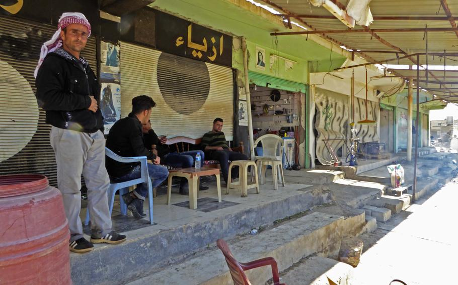 Mulasm Ali stands in front of a shop where Bassam Makhmoud sells snack items, cigarettes and alcohol in the village of Bahzani, Monday March 6, 2017. The men say the village is safe, but they wonder about a future that they say could see a resurgent Islamic State group under a new name.