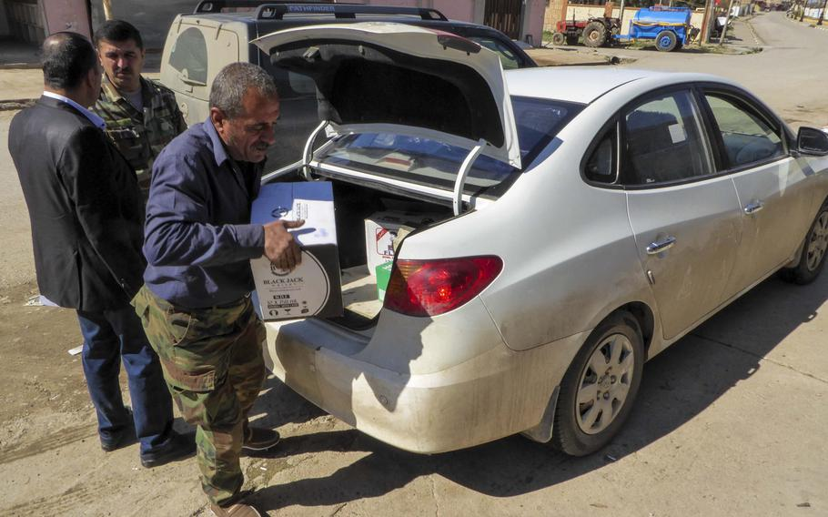 Bassam Makhmoud unloads a box of Black Jack whiskey from his brother's car in front of a shop where they sell alcohol and convenience items in the village of Bahzani, Monday, March 6, 2017. The village was liberated in November, and families and businesses have begun to return to the war-ravaged community after 2 1/2 years of Islamic State occupation.