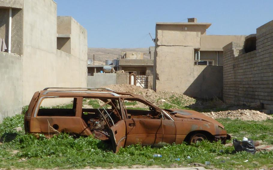 A rusted station wagon sits among the weeds in Bashiqa, Iraq, pictured here on Monday, March 6, 2017.