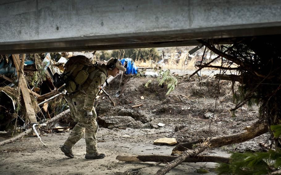 An airman looks for trapped survivors at Sendai Airport, Japan, March 16, 2011, days after a 9.0-magnitude earthquake and related tsunami stuck the region.