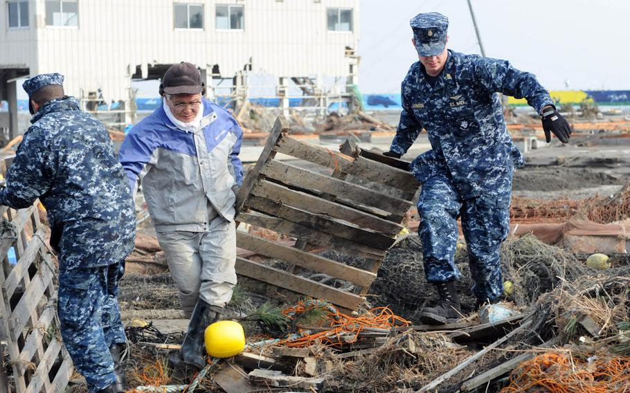 Sailors assigned to Naval Air Facility Misawa, Japan, help remove debris during a cleanup effort at the Misawa Fishing Port, March 14, 2011. More than 90 sailors volunteered to help clean up after an earthquake and tsunami.