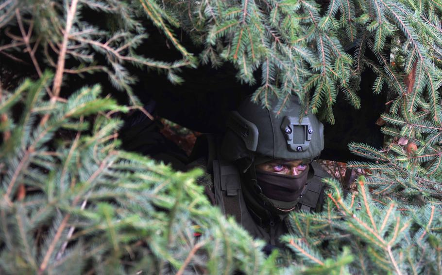 A Lithuanian soldier observes artillery fire from inside a camouflaged enclosure during Exercise Dynamic Front on Wednesday, March 8, 2017.