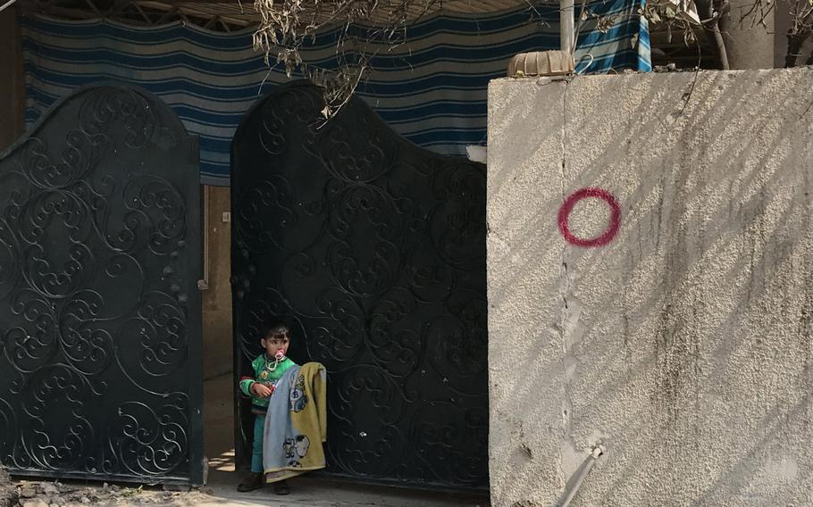A child stands in front of a driveway gate at a home in the al-Dandan neighborhood of Mosul on Wednesday, March 8, 2017. The red circle on the wall marked the house as having a covered driveway suitable for concealing an Islamic State car bomb, residents say.