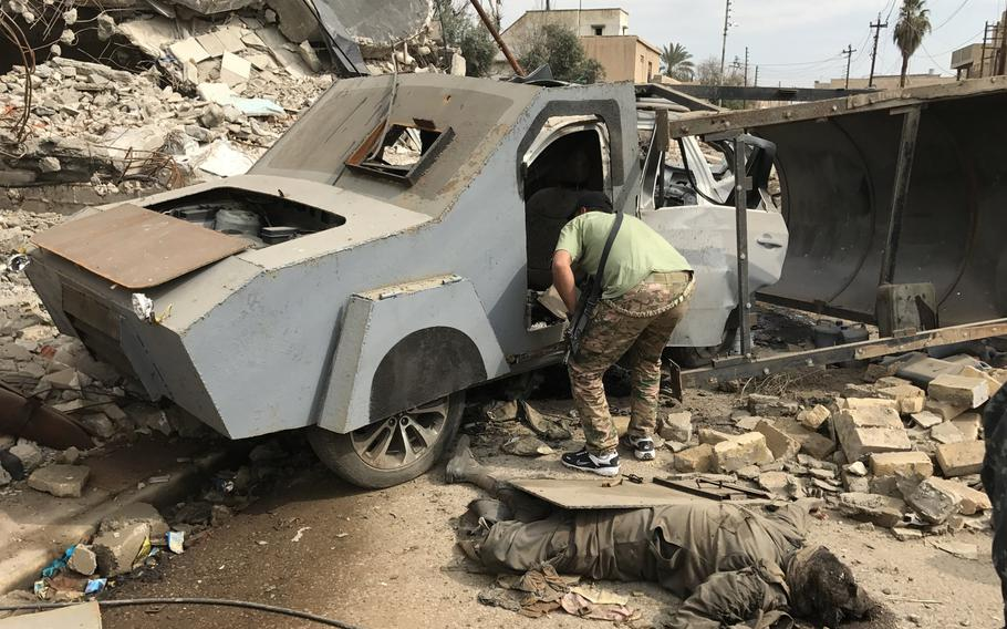 An Iraqi soldier peeks inside an up-armored car bomb on a street in a Mosul neighborhood on Wednesday, March 8, 2017. Iraqi forces stopped the suicide bomber, dead on the ground, before he had a chance to detonate his deadly SUV.