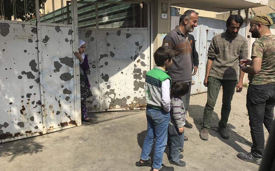 A girl looks on from a gate as men talk in a neighborhood in western Mosul on Wednesday, March 10, 2017.