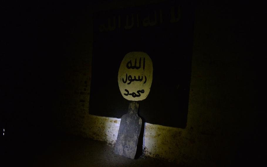 Pictured here on Thursday, March 9, 2017, a marksmanship target leans against a painting of the Islamic State flag on the wall of a railway tunnel that the Islamic State group turned into a covert training base.