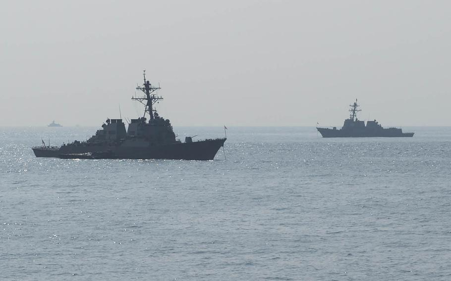 The guided-missile destroyers USS Curtis Wilbur, left, and USS Mustin are anchored off the Korean coast in October 2015.